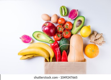 Healthy food background. Healthy food in paper bag fruits and vegetables on white. Vegetarian food. Shopping food supermarket concept. Top view
