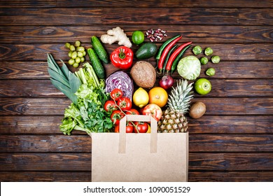 Healthy food background. Healthy food in paper bag pasta, vegetables and fruits on wooden background. Shopping vegetarian food supermarket concept. Top view. copy space