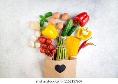 Healthy food background. Healthy food in paper bag vegetables, pasta, eggs, cheese and mushrooms on white. Ingredients for cooking italian pasta. Shopping food supermarket concept. Top view