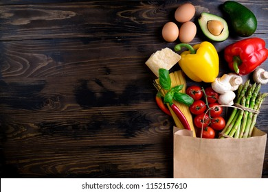 Healthy food background. Healthy food in paper bag vegetables, pasta, eggs, cheese and mushrooms on dark. Ingredients for cooking pasta. Shopping food supermarket concept. Top view