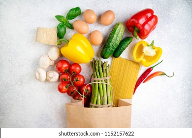 Healthy food background. Healthy food in paper bag vegetables, pasta, eggs, cheese and mushrooms on white. Ingredients for cooking pasta. Shopping food supermarket concept. Top view