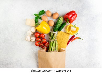 Healthy food background. Healthy food in paper bag vegetables, pasta, eggs, cheese and mushrooms on white. Ingredients for cooking pasta. Shopping food supermarket concept