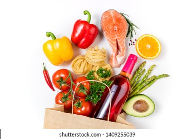 Healthy food background. Healthy food in paper bag fish, vegetables, fruits and wine on white background. Shopping food supermarket concept. Healthy eating, cooking dinner concept