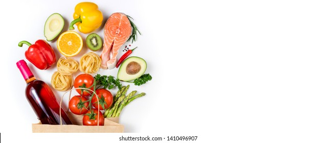 Healthy food background. Healthy food in paper bag fish, pasta, vegetables, fruits and wine on white background. Shopping food supermarket concept. Healthy eating, cooking dinner concept