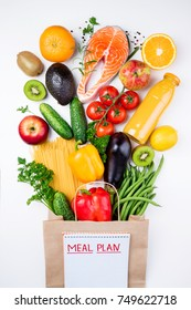 Healthy food background. Healthy food in paper bag fish, vegetables and fruits on white. Shopping food concept. Top view