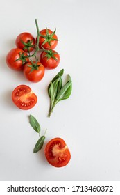 Healthy food background - raw tomatoes and wild herbs on white background, vibrant colours, vitamin food