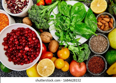 Healthy food background, trendy Virus protection food, coronavirus, immunity concept. Alkaline diet products - fruits, vegetables, cereals, nuts, oils, dark grey concrete background. Top view.