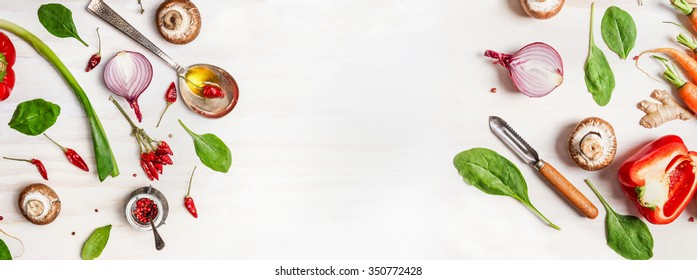 Healthy food background with various vegetables ingredients, spoon with oil and peeler, top view