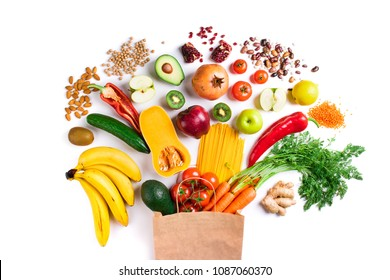 Healthy food background. Healthy vegetarian food in paper bag pasta, vegetables and fruits on white top view. Shopping food in supermarket concept