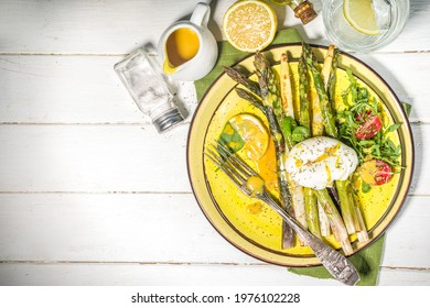 Healthy food, baked grilled asparagus, poached egg and hollandaise sauce  on white wooden background copy space top view
