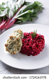 Healthy food. Beetroot rice with chicken cutlet, rosemary on a white plate on a light grey background. Beet tops. risotto. Red rice. Background image, copy space