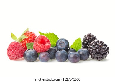Healthy food berries group. Macro shot of fresh raspberries, blueberries, blackberries and strawberry with leaves isolated on white background.