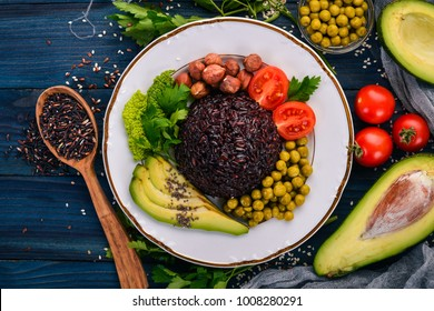 Healthy food. Black rice, avocado, cherry tomatoes, green peas and hazelnut. On a wooden background. Top view. Free space for your text.