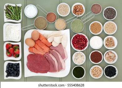 Healthy food for body builders with meat, salmon, supplement powders, dairy, nuts, seeds, fruit, pulses, herbs, grains and cereals on wooden green background.