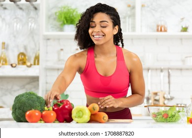 Healthy Food To Boost Your Immune System. Smiling black girl cooking salad at home in loft kitchen interor, copy space