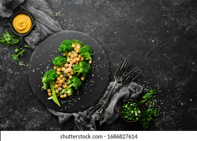 Healthy food: Broiled broccoli, chickpeas and sesame on a black stone plate. Top view. Free space for text.