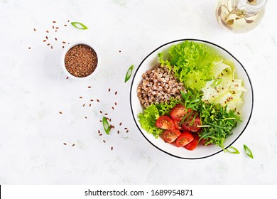 Healthy food. Buckwheat salad with cherry tomatoes, daikon, red onion and fresh herbs. Vegan food. Diet menu.  Top view, copy space, flat lay