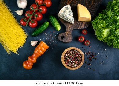 Healthy food. Cheese on a wooden board and other food lying on the background of concrete