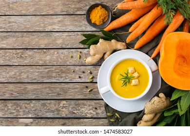 Healthy food, clean eating concept. Seasonal spicy fall vegetables creamy pumpkin and carrot soup with ingredients on a rustic wooden table. Top view flat lay copy space background