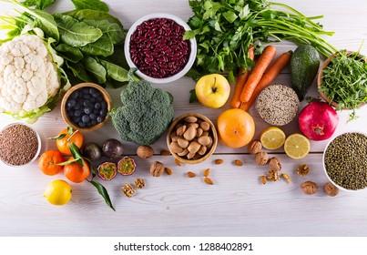 Healthy food clean eating: fruit, vegetable, seeds, superfood, cereals, leaf vegetable on black wood background with copy space, top view.