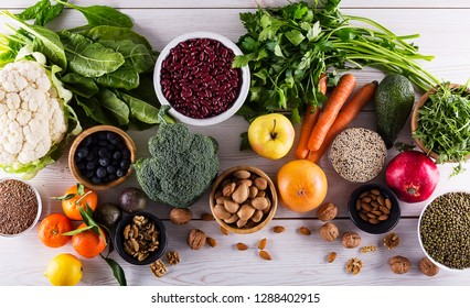 Healthy food clean eating : fruit, vegetable, seeds, superfood, cereals, leaf vegetable on black wood background with copy space, top view.