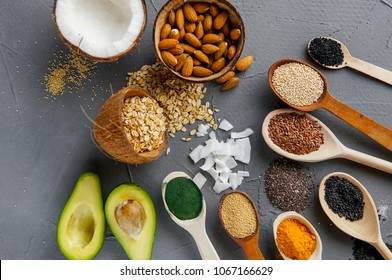 Healthy food clean eating: seeds, superfood, cereal, nuts and fruits over gray concrete background, copy space