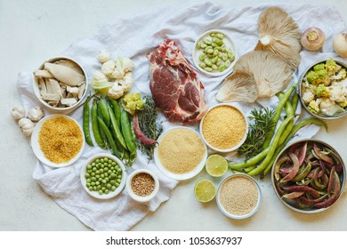 Healthy food clean eating selection pork meat mushrooms fresh vegetables cereals dried goods overhead white table