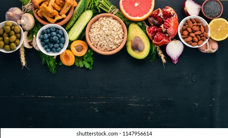 Healthy food clean eating selection: Vegetables, fruits, nuts, berries and mushrooms, parsley, spices. On a black background. Free space for text.