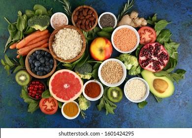 Healthy food clean eating selection: fruit, vegetable, seeds, superfood, cereals, leaf vegetable on background