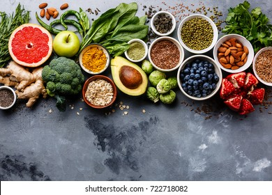 Photo of Healthy food clean eating selection: fruit, vegetable, seeds, superfood, cereals, leaf vegetable on gray concrete background copy space
