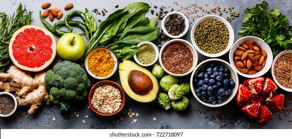 Terveellinen ruoka puhdas syöminen valinta: hedelmät, vihannekset, siemenet, superfood, vilja, lehtikasvis harmaalla betonilla taustalla