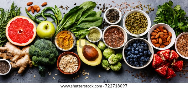 Healthy food clean eating selection: fruit, vegetable, seeds, superfood, cereal, leaf vegetable on gray concrete background