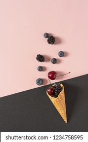 Healthy food composition. Blueberries, cherries and blackberries in a waffle cone on pastel pink and black or grey background. Holiday concept. Flat lay, top view, copy space