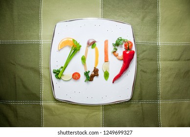 Healthy food composition made of fresh fruit and vegetables which create number 2019 on a plate. New year healthy diet concept.