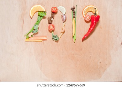 Healthy food composition made of fresh fruit and vegetables which create number 2019 on wooden board. New year healthy diet and lifestyle concept.