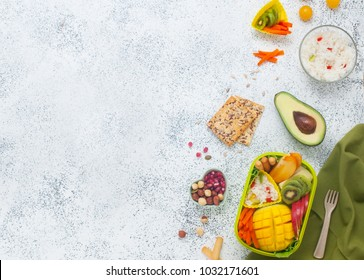 Healthy food concept: Close up of open lunch box with rice, fresh fruits and vegetables on the grey background with blank space for text; top view, flat lay