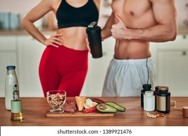 Healthy food concept. Cropped image of attractive sporty woman and handsome muscular man on kitchen. Hard choice between healthy food full of protein and sport supplements. Sports nutrition.