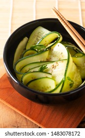 Healthy Food concept Cucumber Salad with soy sauce and Sesame Dressing in black bowl with copy space