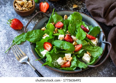 Healthy food concept, Diet salad plate. Summer salad with strawberries, fetacheese and walnut on a stone countertop.