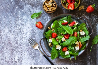 Healthy food concept, Diet salad plate. Summer salad with strawberries, fetacheese and walnut on a stone countertop. Top view flat lay background. Copy space.