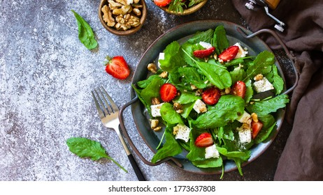 Healthy food concept, Diet salad plate. Summer salad with strawberries, fetacheese and walnut on a stone countertop. Top view flat lay background. Banner.