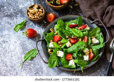 Healthy food concept, Diet salad plate. Summer salad with strawberries, fetacheese and walnut on a stone countertop. Copy space.