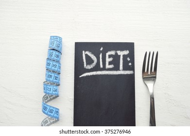 Healthy food concept. Fork, knife and tape measure on wooden table. Top view with copy space.