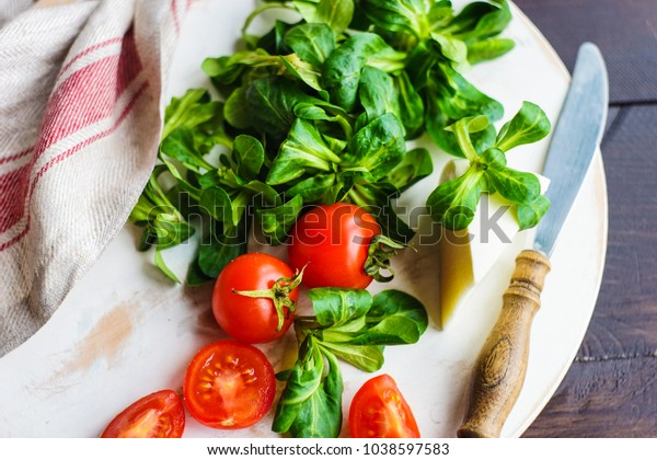 Healthy food concept - fresh corn salad leaves, cheese annd tomatoes on rustic background wih copyspace
