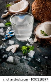 Healthy food concept.  Fresh Organic Coconut Water with coconuts, ice cubes and mint, on rusty dark blue background, copy space