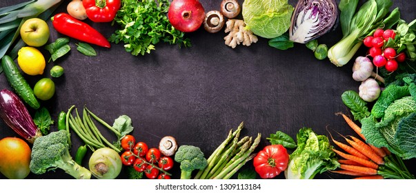 Healthy food concept with fresh vegetables and ingredients for cooking. Top view with copy space. Dark background