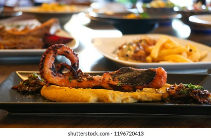 Healthy food concept. Grilled tentacle of octopus for appetizer on black plate. Blur plates with foods background, closeup.