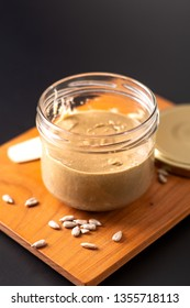 Healthy food concept homemake sunflower butter in glass jar by organic sunflower seeds on black background