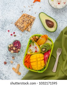 Healthy food concept: lunch box with rice, fresh fruits and vegetables on the grey background with blank space for text; top view, flat lay