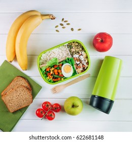 Healthy food concept: Lunch box filled with rice, mixed vegetables, boiled egg and nuts on white wooden background; top view, flat lay